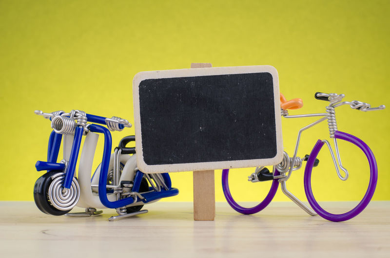 travel concept, miniature handcrafted scooter and bicycle on wooden desk shot over lighting effect Transportation Yellow Still Life Indoors  Technology No People Land Vehicle Mode Of Transportation Copy Space Connection Wireless Technology Wall - Building Feature Flooring Stationary Communication Bicycle Medical Equipment Close-up Wheel