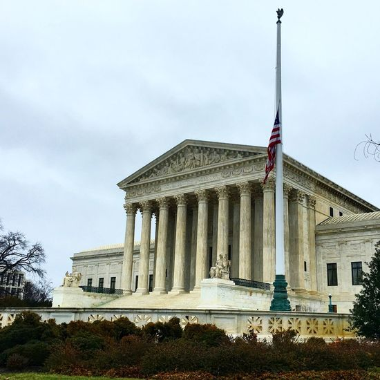 American flag at supreme court against sky
