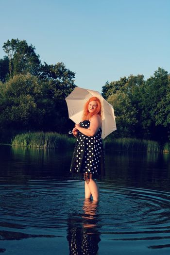 Redhead Woman Holding Umbrella In Lake Against Sky