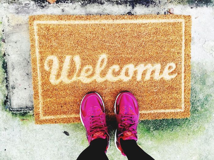Welcome Sneakers Fresh Entrance Welcome Welcoming New Beginnings New Start Positive Emotion Positive Positive Emotion New New Start Positive Low Section Shoe Real People One Person Human Leg Standing Body Part Human Body Part Personal Perspective Directly Above High Angle View Unrecognizable Person Pink Color Mat Outdoors