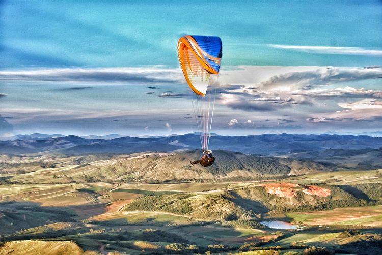 Kite flying over landscape against sky