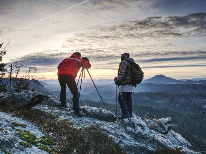 Couple hiking photographers on view point above forest, taking photos and looking on sunset