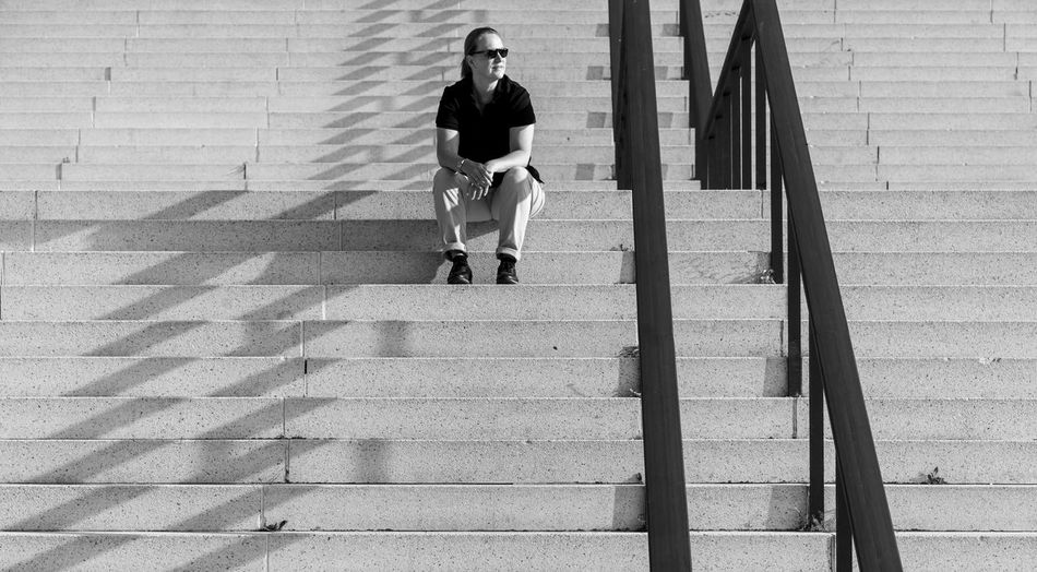 Full length of woman wearing sunglasses sitting on steps