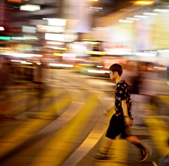 Blurred motion of woman walking on road at night