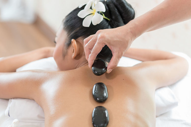 Cropped image of therapist placing hot stones on woman back