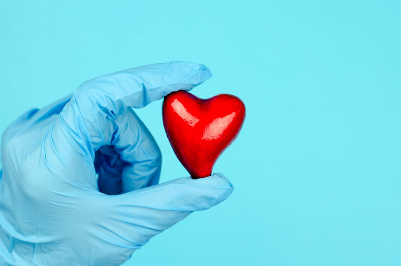 Close-up of hand holding heart shape over white background