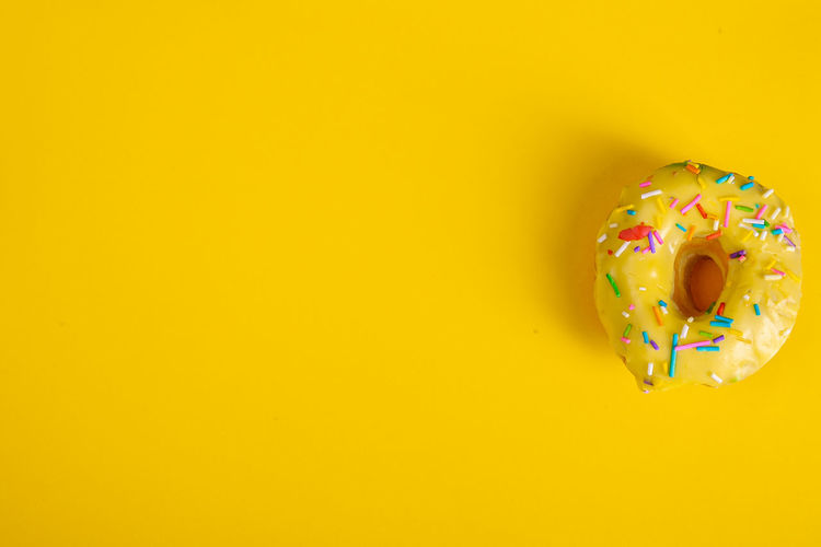 High angle view of multi colored candies against yellow background
