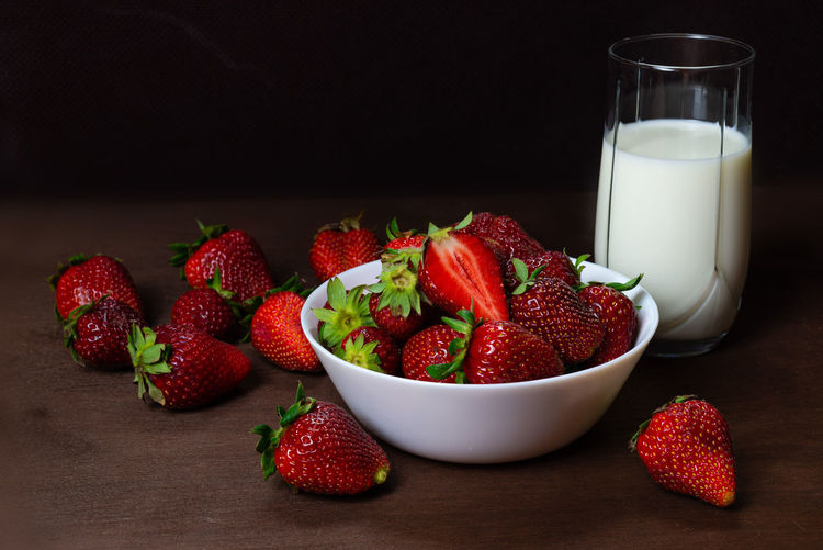 Fresh strawberries in ceramic bowl and a glass of milk on dark wooden background. Selective focus. Food And Drink Food Freshness Red Indoors  Still Life No People Strawberry Strawberries Fruit Fruits Fresh Healthy Eating Vehetable Natural Raw Vitamin Raw Food Tasty Breakfast Ripe Juicy Sweet Berry Delicious Nutrition Background Rustic Dessert Freshness Eating Organic Close-up Diet Ingredient Vegan Snack Apperitive Pattern Dark Wooden Table Brown Texture Textured  Bowl Plate Ceramic Milk Glass Berry Fruit Wellbeing Dairy Product Drink Refreshment Black Background Dieting