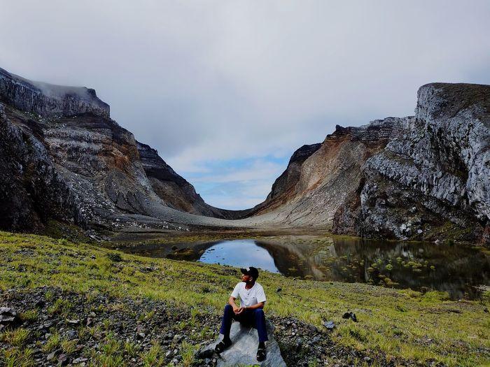 Full length of man sitting on rock against mountain