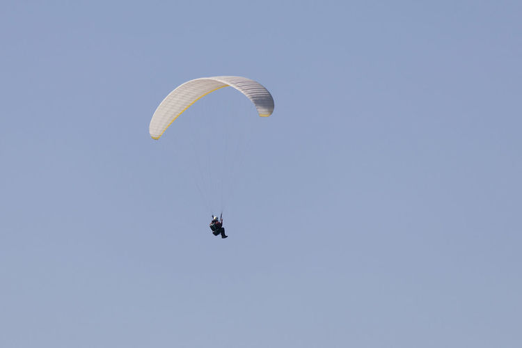 Low angle view of man paragliding against clear sky