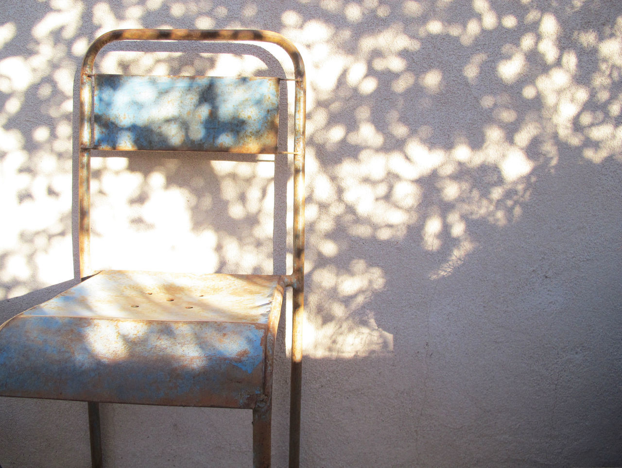 Rusty Chair Against Wall With Shadow