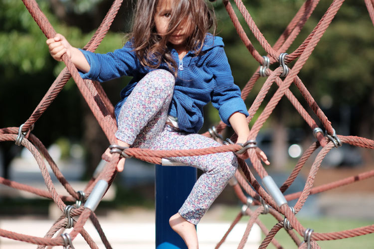 Portrait Of Girl Climbing Rope At Park