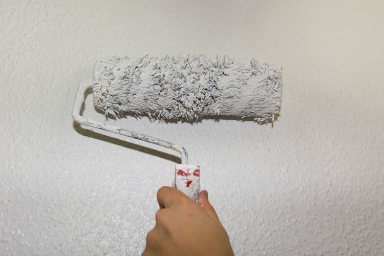 Cropped hand of person holding paint roller against wall