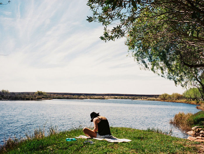 Female sitting at the waters edge relaxing and reading 35mm 35mm Film Beauty In Nature Female Film Grass Hat Holiday Lake Landscape Landscape_Collection Nature One Person Outdoor Outdoors Reading Relaxation River Sitting Summer Towel Tree Water Wilderness Young Adult