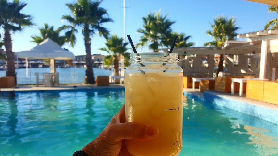 Cropped hand holding lemonade in jar against swimming pool