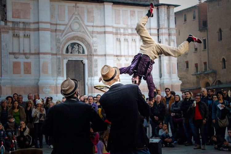 Man Performing While Crowd Looking At Him In Front Of Bologna Cathedral