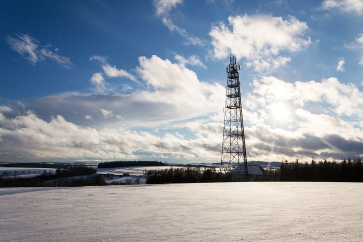 Communications tower on field against sky