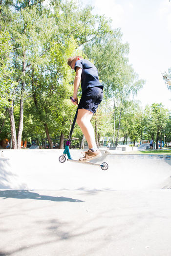 boy riding a scooter in a skatepark Full Length Leisure Activity Tree One Person Skateboard Sports Equipment Sport Real People Transportation Casual Clothing Plant Day Motion Nature Sunlight Lifestyles Balance Push Scooter Men Skill  Riding
