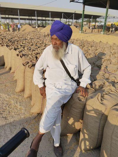 Mature man wearing turban sitting on sack at warehouse