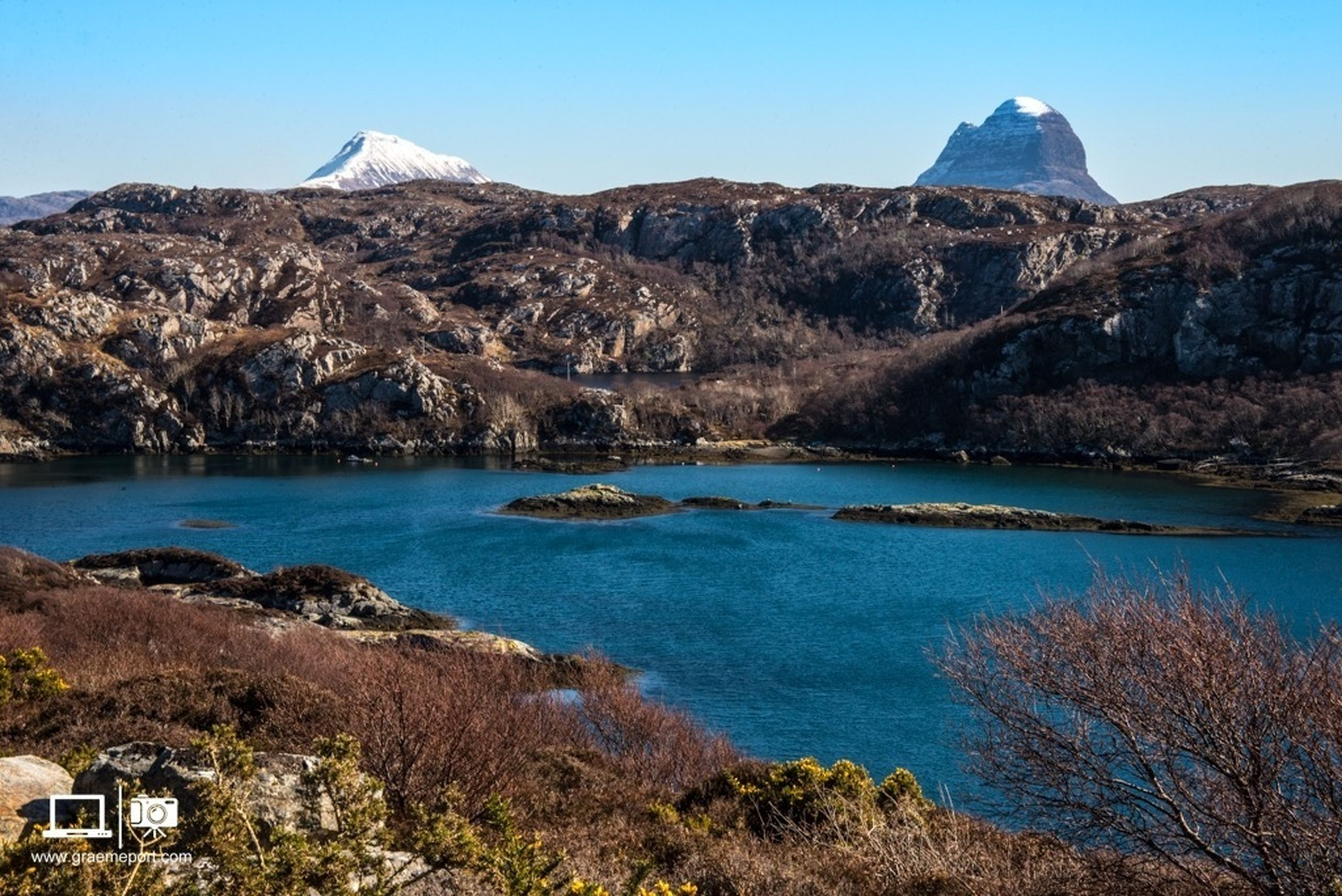 mountain, water, clear sky, blue, tranquil scene, scenics, tranquility, beauty in nature, mountain range, nature, rock - object, lake, rock formation, tree, sea, idyllic, non-urban scene, sky, day, sunlight
