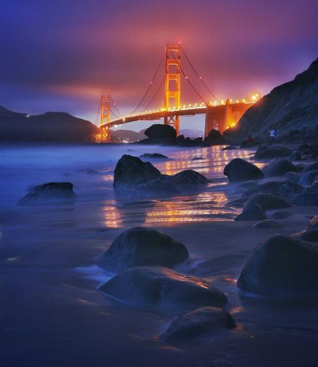 Illuminated golden gate bridge over bay at night