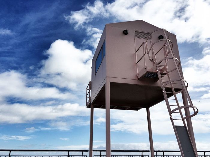 Low Angle View Of Lifeguard Hut Against Cloudy Sky