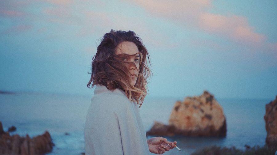 Woman Smoking At Beach Against Sky