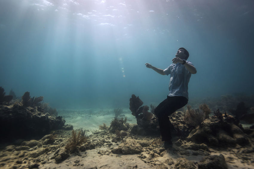 Young adult man fully dressed on bottom of the ocean Business Attire Clothed  Conceptual Conceptual Photography  Full Length Lifestyles Marine Nature Ocean One Person Real People Sea Swimming UnderSea Underwater Water
