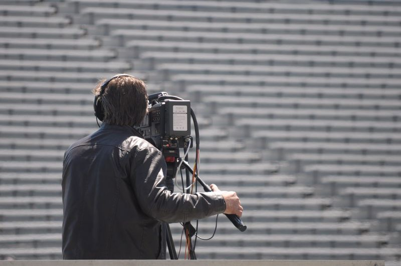 Man with television camera standing in stadium
