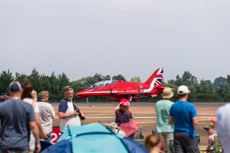 A single Red Arrow BAE systems Hawk T1 of the Royal Air Force taxiing on the runway at RIAT Fairford 2018, UK, with spectators looking on. 100 Years Air Tattoo Airshow BAE Systems Hawk T1 Fairford Hawk T1 RIAT Royal International Air Tattoo Aerobatics Air Display  Aircraft Airplanes Aviation International Landed Open Air Pilot Public Public Access Red Paint Red Plane Runway Taxing Viewing Weekend Real People Group Of People Men Large Group Of People Women Patriotism Day Lifestyles Transportation Flag Adult Crowd Leisure Activity Sky Pride Nature Mode Of Transportation Group Outdoors Independence Spectator