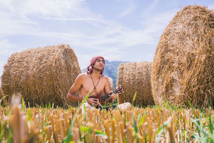 Grass Hay Field Hay Bale The Portraitist - 2018 EyeEm Awards Agriculture Bale  Day Dreamlike Field Folk Front View Hay Bales Headband Leisure Activity Musician One Person Outdoors Playing Rural Scene Sitting Straw Straw Bales Three Quarter Length Ukulele Young Adult