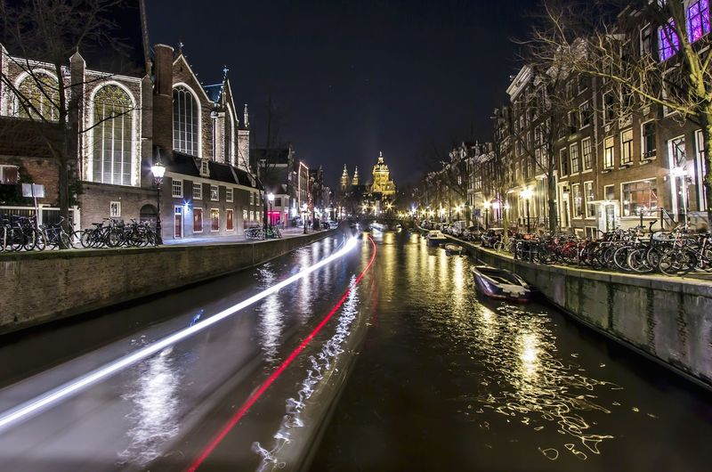 Light trails in canal amidst buildings in city against clear sky