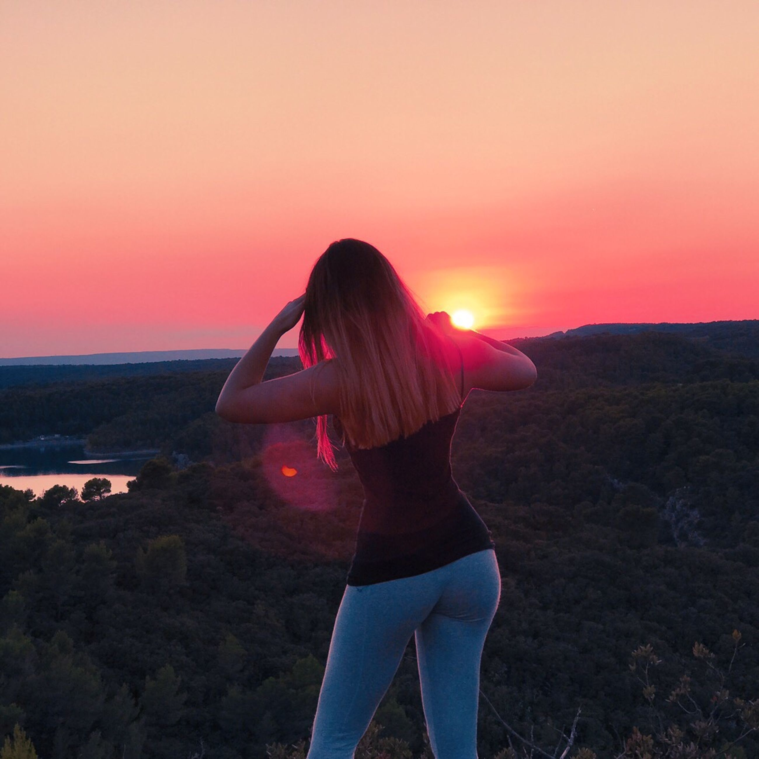 sunset, standing, person, rear view, scenics, sea, long hair, idyllic, horizon over water, water, leisure activity, tranquil scene, tranquility, getting away from it all, beauty in nature, three quarter length, tourist, sun, vacations, weekend activities, remote, cliff, city life, non-urban scene, nature, sky, tourism, majestic, solitude, outdoors