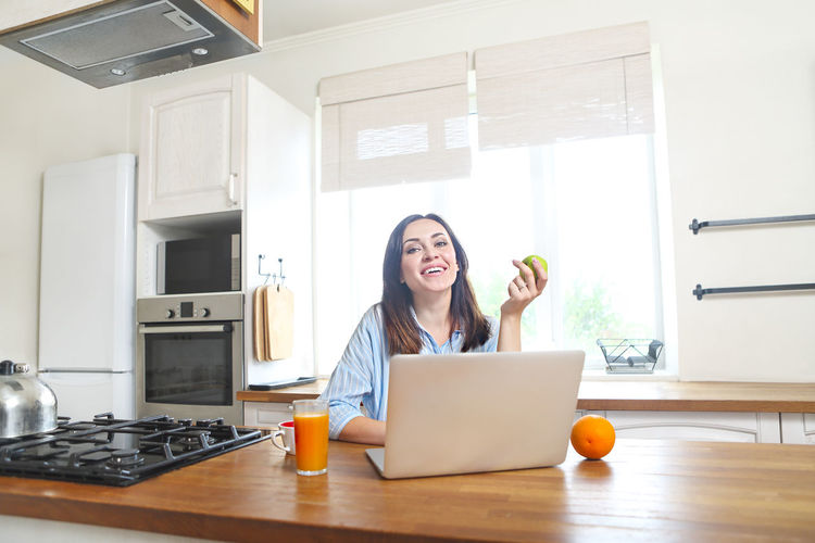 Cheerful woman using laptop in kitchen at home
