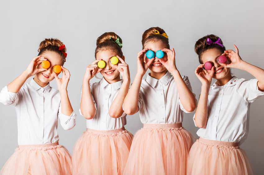 Beautiful teenage model girls in pink tutu or tulle skirts with macaroons, fancy cakes and sweets in studio on white background Cakes Celebration Event Fun Models Child Childhood Girls Group Of People Hairstile Indoors  Party Scirt Smile Studio Shot Sweets Teenager