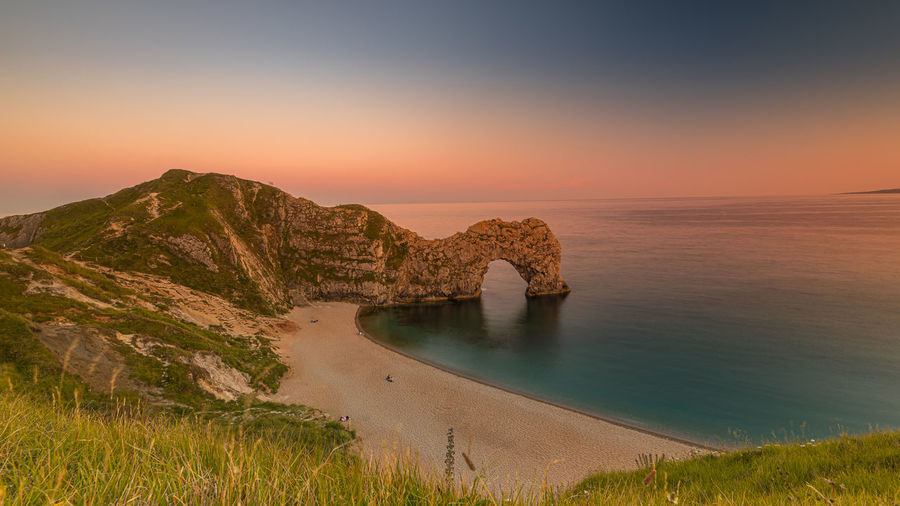 Scenic view of sea against sky during sunset at durdle door in dorset