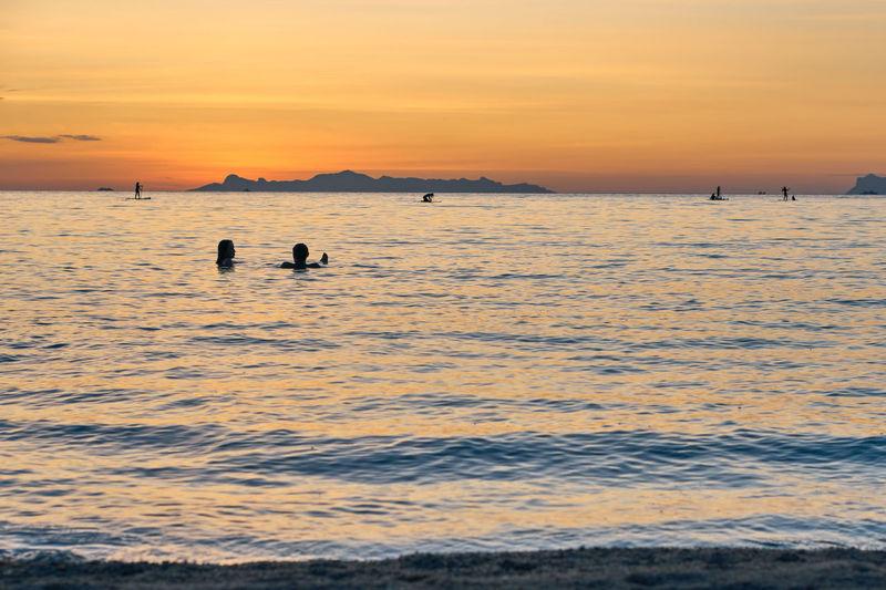 Silhouette people swimming in sea against orange sky