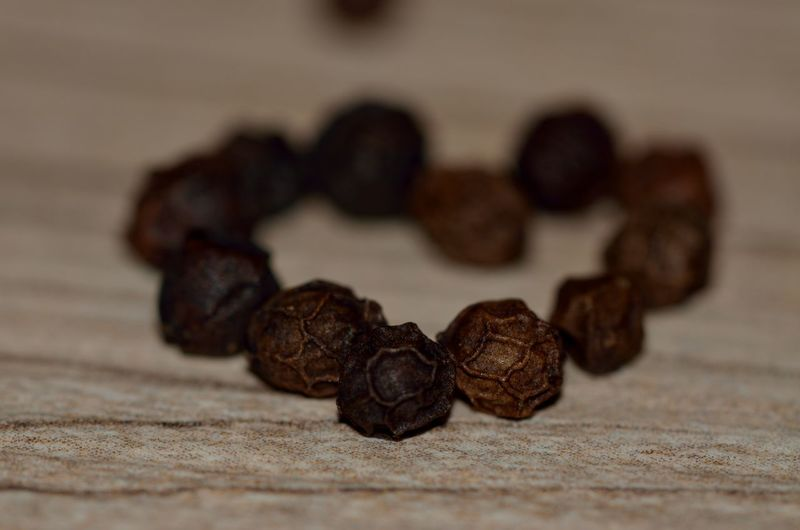 Close-up of heart shape made up of black peppercorn on table