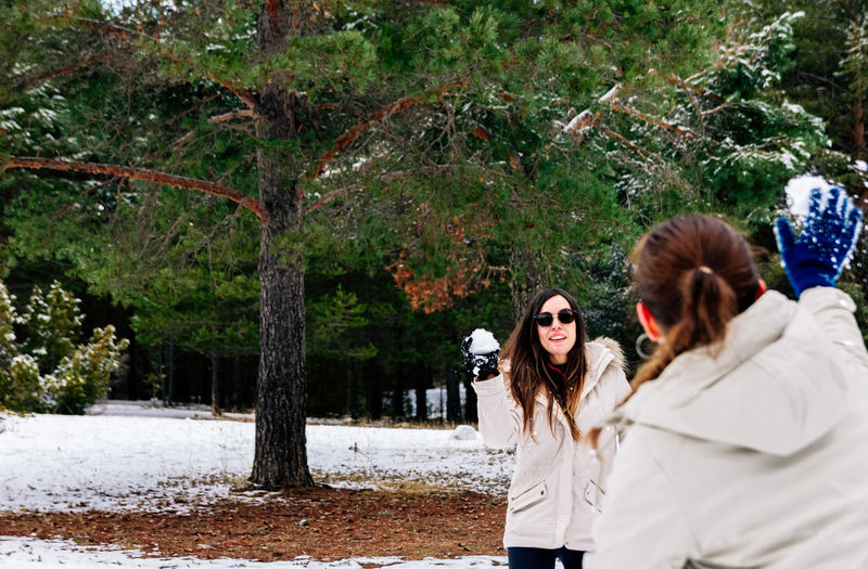 Rear view of woman playing snow fight with friend during winter