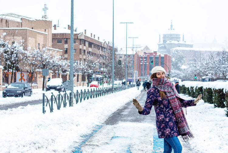 Woman walking on snow covered street in city during winter