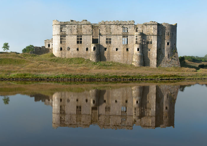 Carew Castle overlooks the tidal mill pond on the Carew River. The north face of the Norman castle was later transformed into an Elizabethan mansion. Carew Castle Elizabethan History No People Norman Old Ruin Outdoors Pembrokeshire Reflection Tree Wales Water Waterfront EyeEmNewHere Tourism
