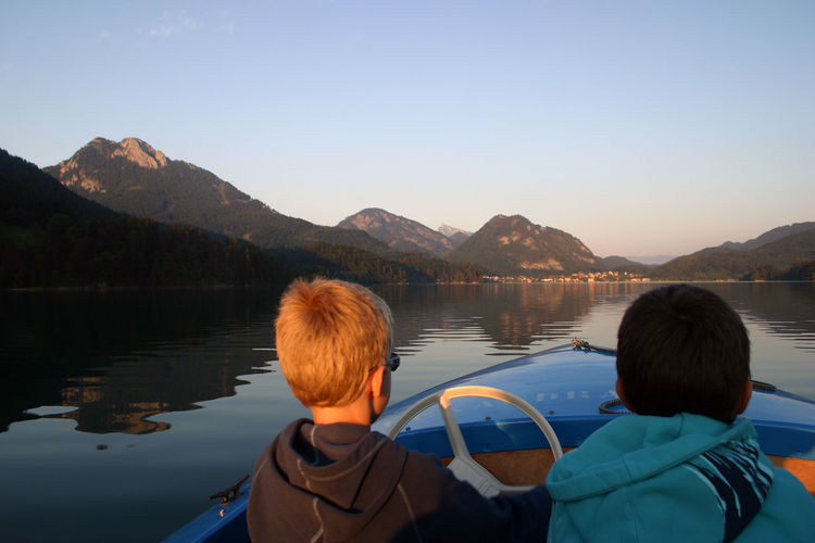Rear view of brothers sitting on boat in lake against clear sky
