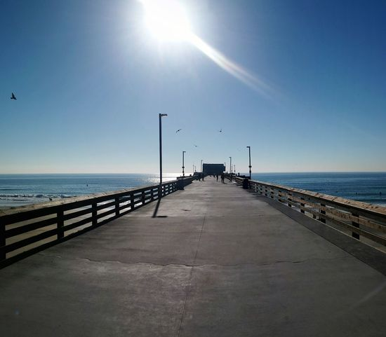 Newport Beach Newport Pier Pier Balboa Peninsula Pacific Ocean Sea Horizon Over Water Sunny Clear Sky Sky Water Sunlight Beach Sun Bird Pier Tranquility Coastal Feature Pacific Coast Life Is A Beach Beautiful Day Perspective Outdoors Sand One Point Perspective