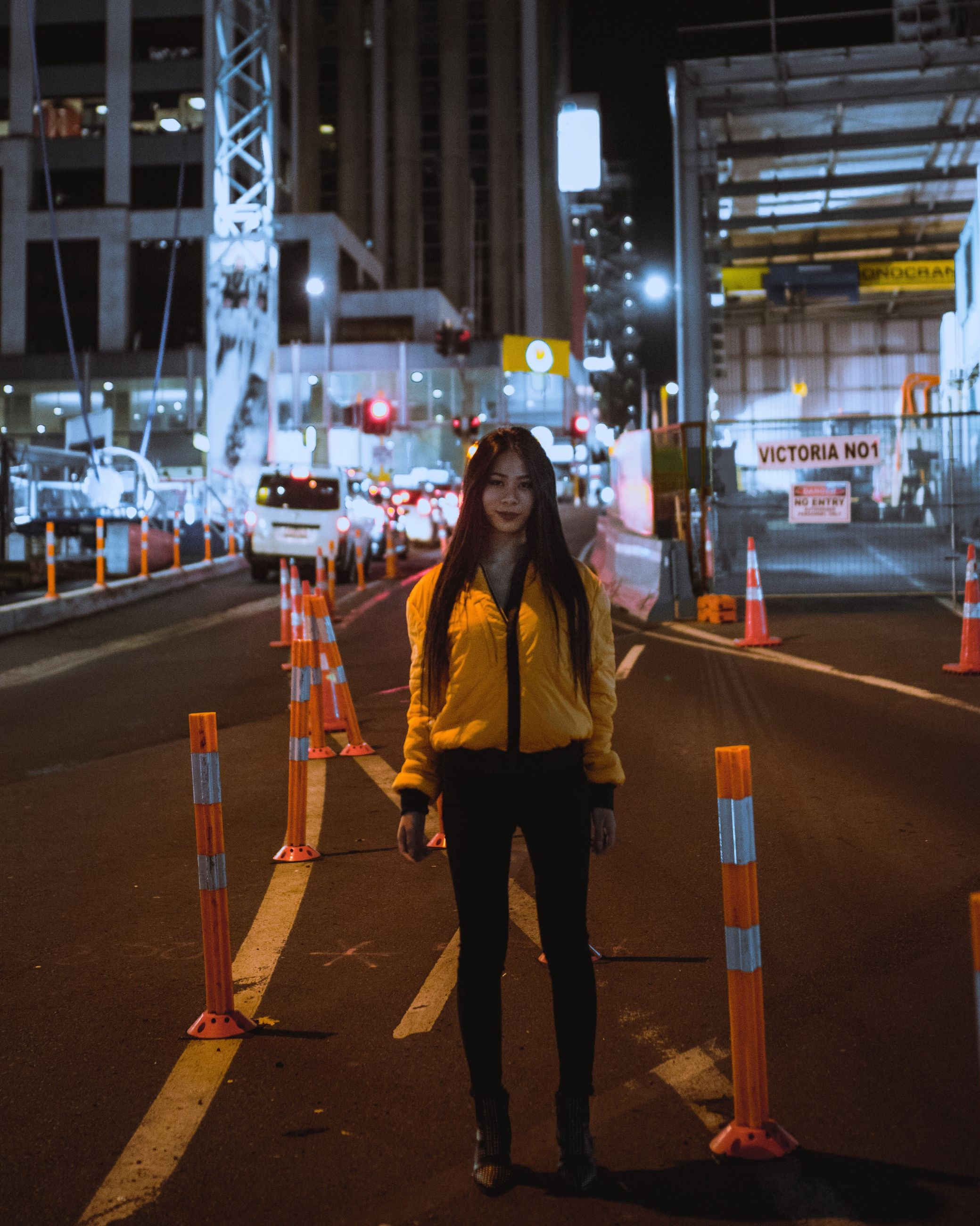 night, full length, illuminated, city, one person, one woman only, standing, city life, real people, only women, outdoors, people, warm clothing, women, adults only, building exterior, adult, one young woman only, technology, cityscape, young adult, bus stop