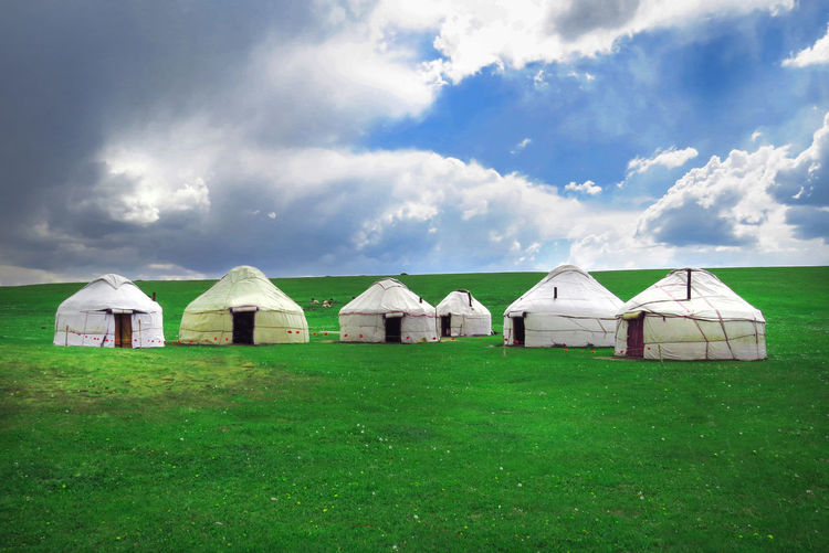 Yurts at Song Kol lake in Kyrgyzstan mountains.The blue sky, beautiful clouds, Kyrgyzstan NOMAD Song Kol, Kyrgyzstan Yurts Architecture Barn Building Building Exterior Built Structure Cloud - Sky Day Environment Field Grass Green Color Land Landscape Nature No People Nomadiclife Outdoors Plant Sky