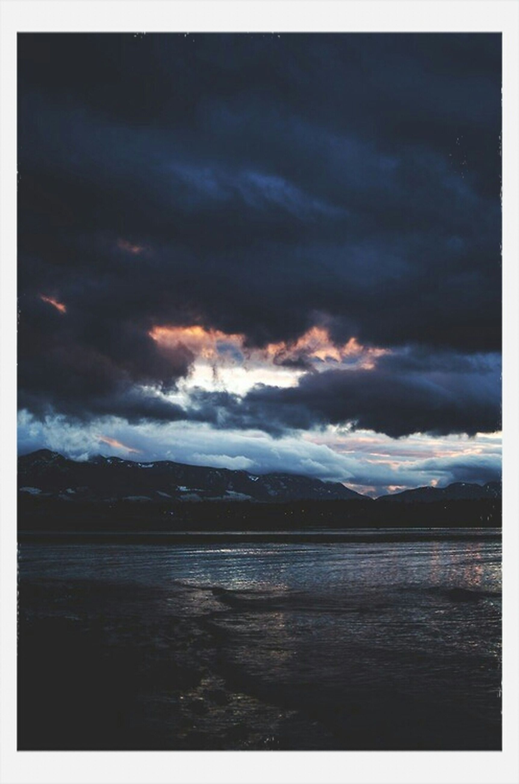 sky, transfer print, water, cloud - sky, cloudy, scenics, tranquil scene, tranquility, auto post production filter, beauty in nature, weather, sea, nature, overcast, cloud, storm cloud, dusk, idyllic, lake, dramatic sky