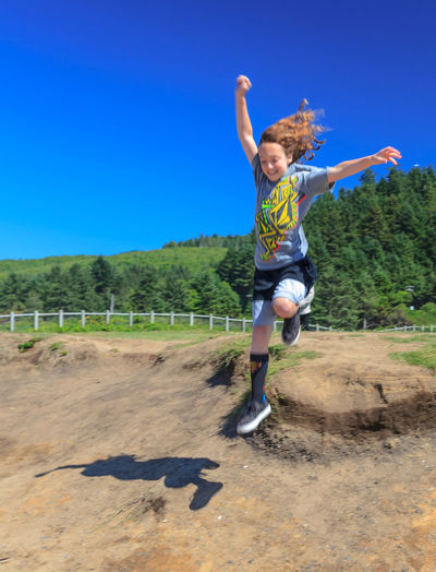 Boy jumping on ground against clear blue sky