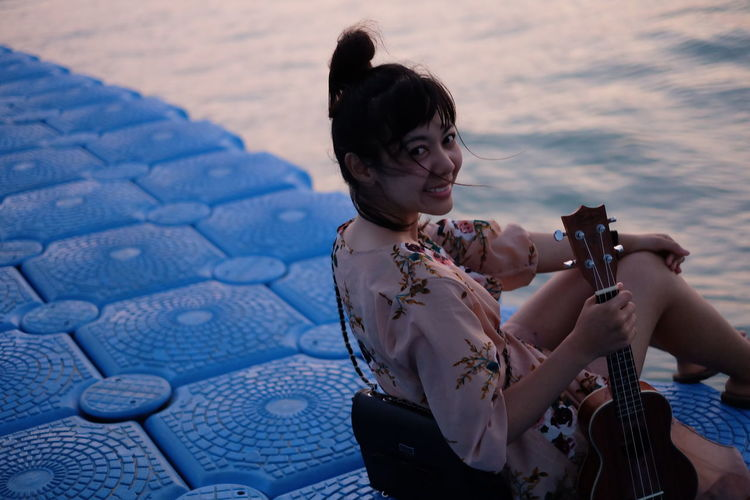 Portrait Of Woman With Guitar Sitting At Beach