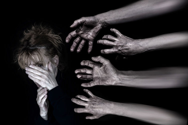 An anxious woman tries to protect herself with her hands. Hands reach for her. Black Background Human Hand Hand Studio Shot Human Body Part Indoors  Adult People Body Part Unrecognizable Person Cooperation Emotion Women Aggression  Phobia Psychosis Schizophrenia Panic Attack Alone Hopeless Fear Attack Bipolar Violence Sad