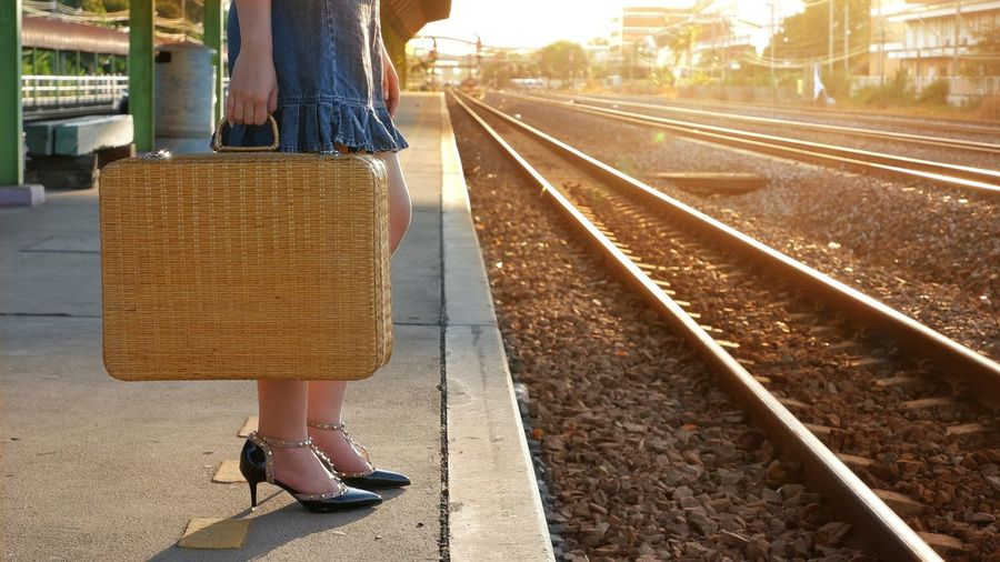 Low section of young female traveler holding vintage bamboo suitcase and waiting for train on platform at railway station with flare light on railroad tracks in evening time Railroad Pretty Alone Lifestyle Tourist Traveler Female Young Waiting High -heeled Shoes Flare Light Evening Platform Bamboo Suitcase Holding Vintage Tone Low Section City Railroad Track Women Rail Transportation Journey Travel Railroad Station Passenger Train Train - Vehicle Public Transportation Station Railroad Platform